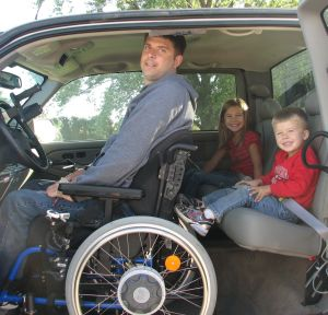 Eric Beckman sitting in wheelchair in pickup truck with his kids in back seat