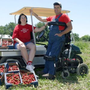 Ed Bell using standing wheelcair in front of golf cart filled with strawberries with wife sitting on cart