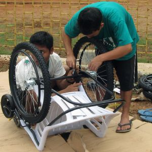 Two young men in India constructing wheelchair out of plastic lawn chair and bicycle tires