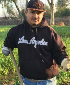 Rosendo Ramirez standing with hoe in a field