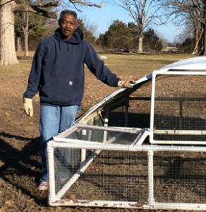 Keith Raspberry standing next to portable chicken coop