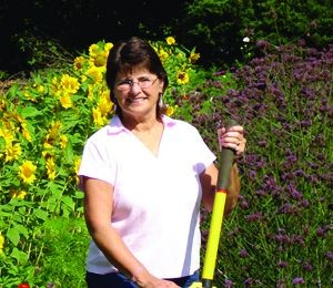 Terrie Webb holding rake in front of red and yellow flower crops