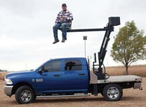 Photo of man sitting on lift attached to bed of pickup truck. He is about 10 feet off the ground.