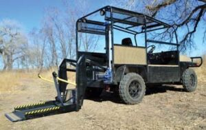 Buddy Buggy utility vehicle with wheelchair lift on back extended to the ground