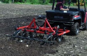 Cultivator on back of utility vehicle being used to break up ground.