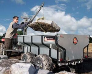 Man using Boom Lift on trailer to hoist large rock into trailer.