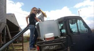 Carey standing on rear of utility vehicle using an auger to put feed into feeder located on back of UTV