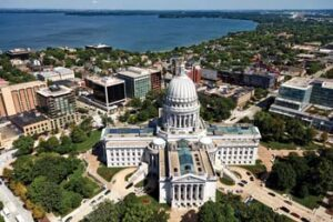 Aerial view of Madison, Wisconsin with state capitol building in foreground and large lake in background.