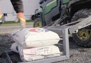Strong Arm lift on side of UTV with seed bags stacked on it.