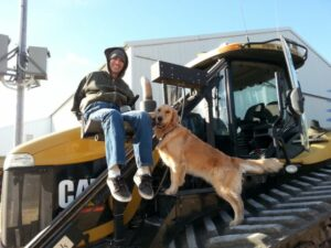 Man sits on lift to get into tracked tractor as dog stands near him on tractor