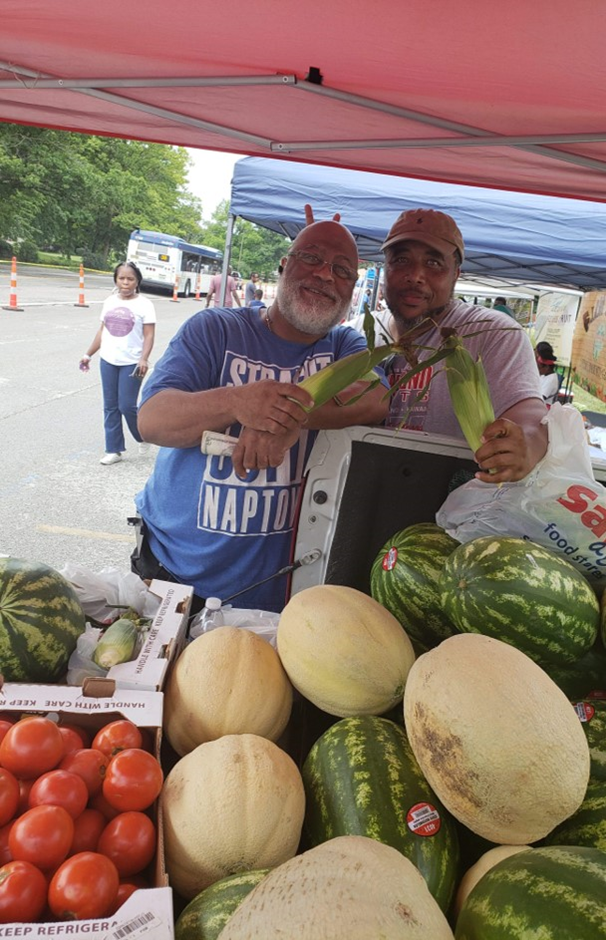 Farmers selling melons and vegetables at a farmers market stand.
