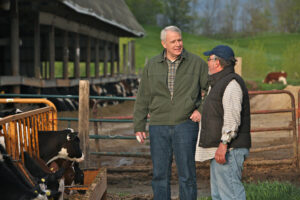 Two men talk outside dairy barn with Holstein cows in background